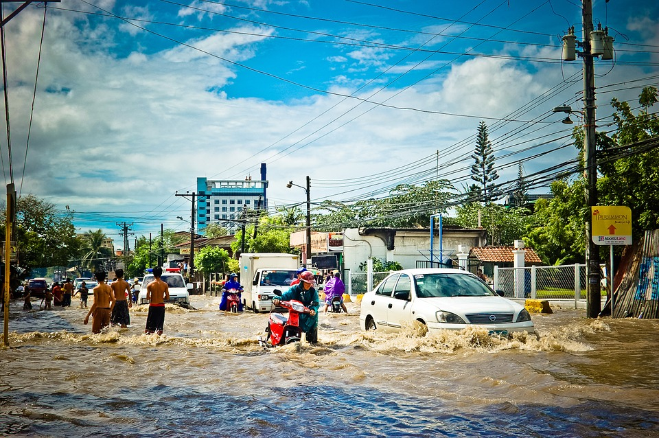 people travelling along a flooded city street